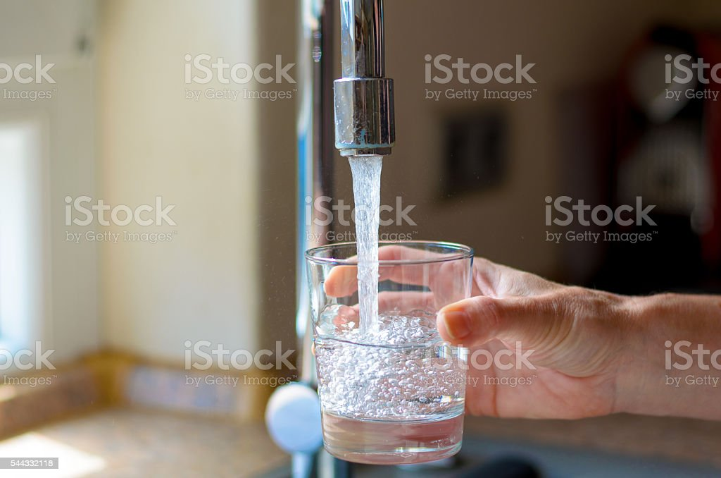 Woman filling a glass of water from a tap royalty-free stock photo