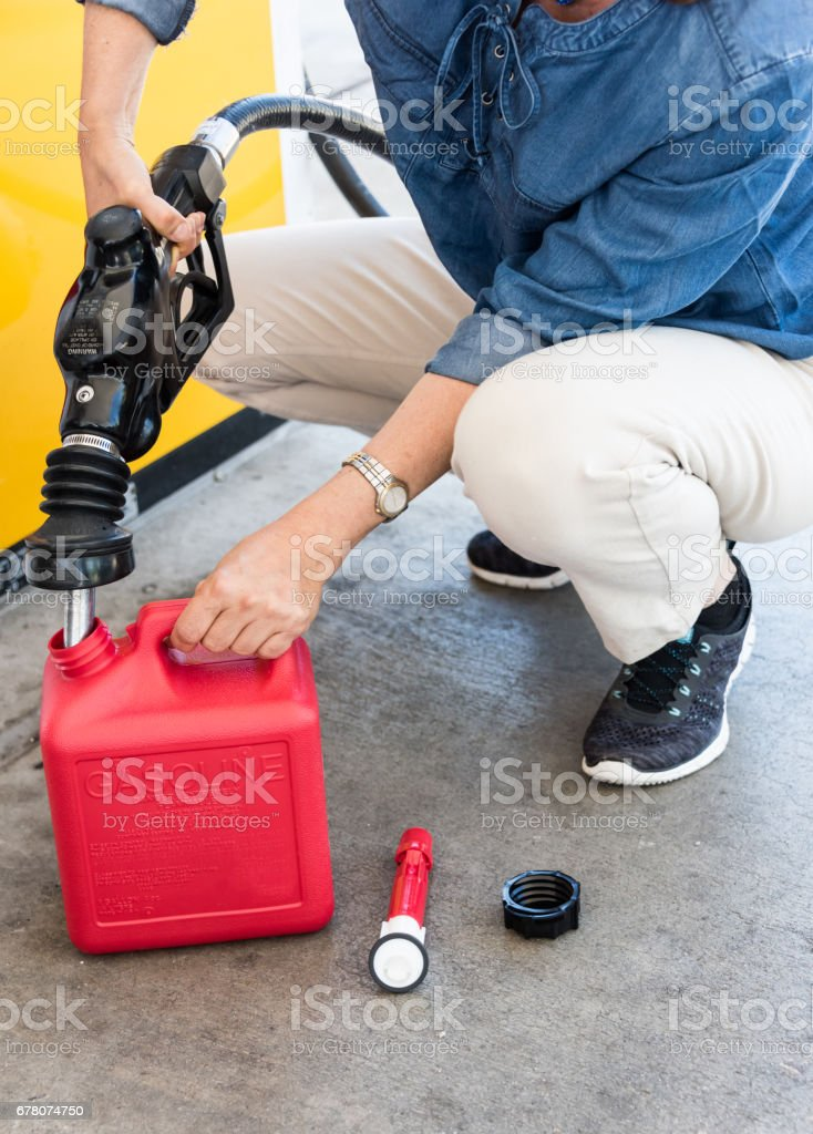 woman filling a small gas can stock photo