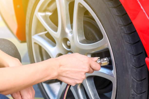 vrouw vullen lucht in de banden van een auto druk op te voeren - tyre stockfoto's en -beelden