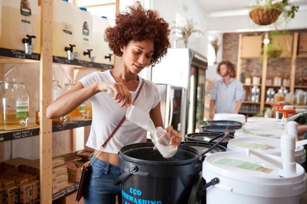 woman filling container with dishwasher powder in plastic free grocery store - rifiuti zero foto e immagini stock