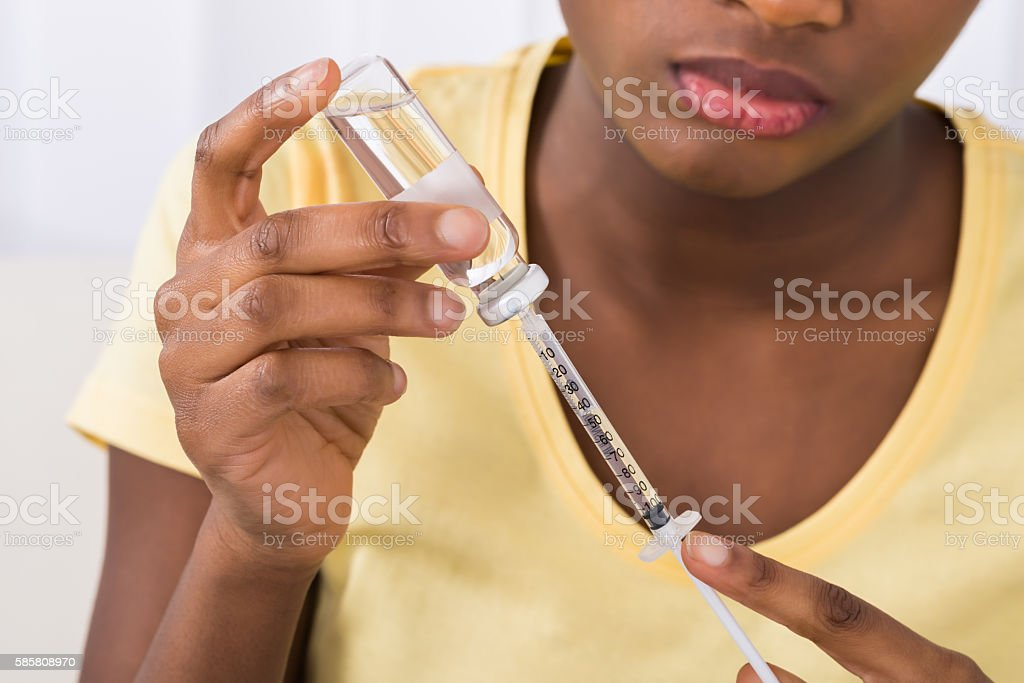 Woman Filling Medicine In Syringe stock photo