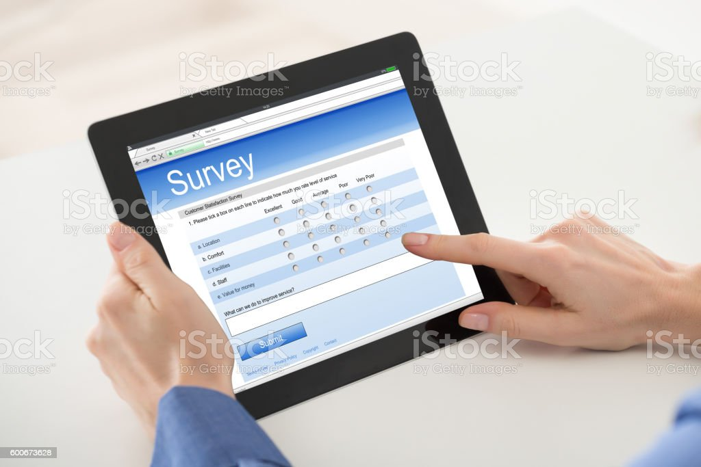 Woman Filling Online Survey Form On Digital Tablet stock photo