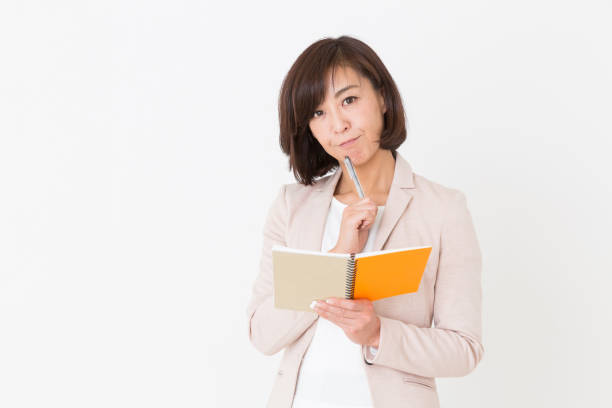 woman filling out a notebook stock photo