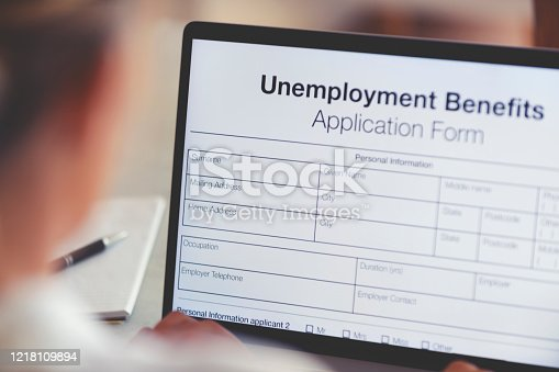 Woman filling out an online unemployment benefits application form. She is using a laptop computer.