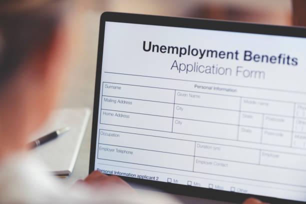 Frau füllt ein Online-Antragsformular für Arbeitslosenunterstützung aus. – Foto
