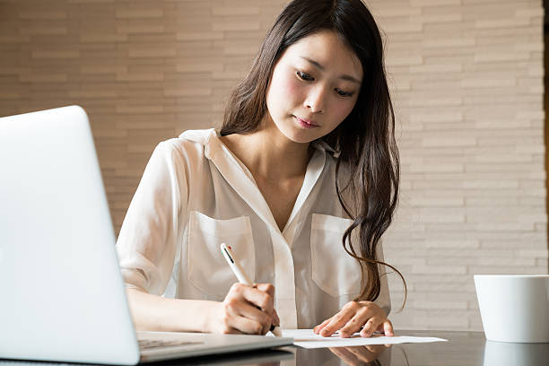 Woman filling out important paper documents Woman filling out important paper documents only japanese stock pictures, royalty-free photos & images