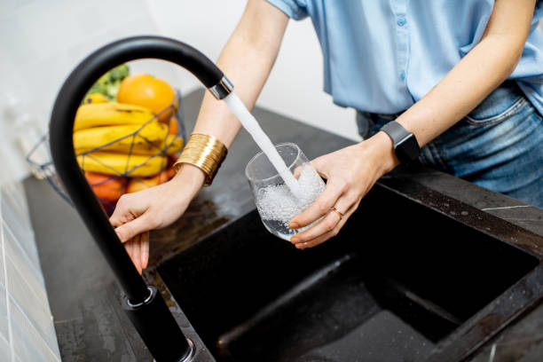 Woman filling tap water on the kitchen Woman filling glass with tap water for drinking on the kitchen drinking water stock pictures, royalty-free photos & images