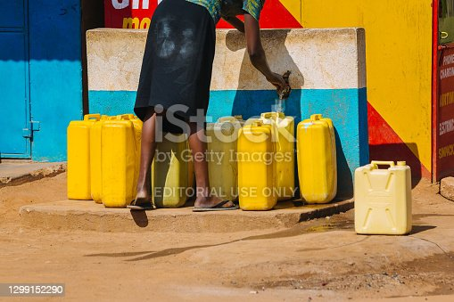 istock Woman filling up water cans at a public water source in Uganda, Africa 1299152290