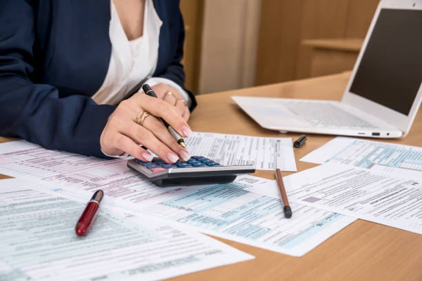 Woman filling US tax form Woman filling US tax form taxes stock pictures, royalty-free photos & images