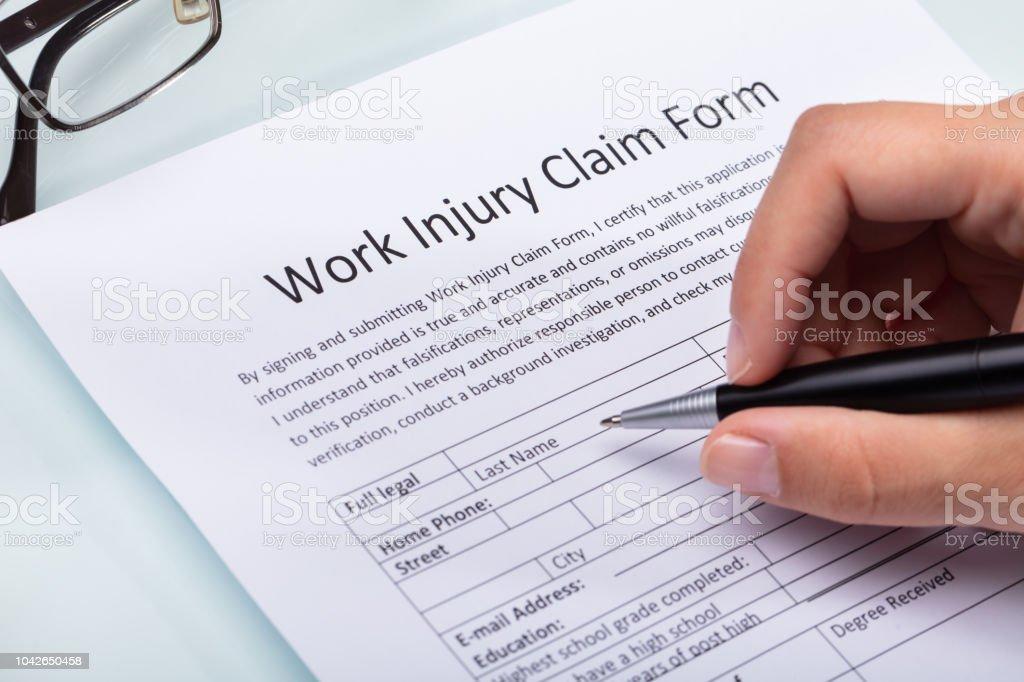 Mujer llenando el formulario de reclamación de lesiones de trabajo foto de stock libre de derechos