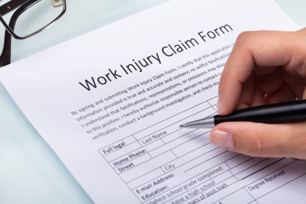 woman filling work injury claim form - soddisfazione foto e immagini stock