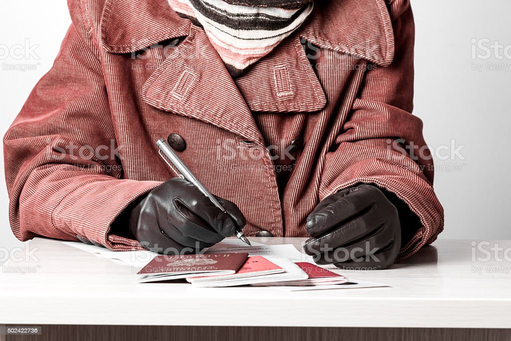 Woman fills the document forms at the table stock photo
