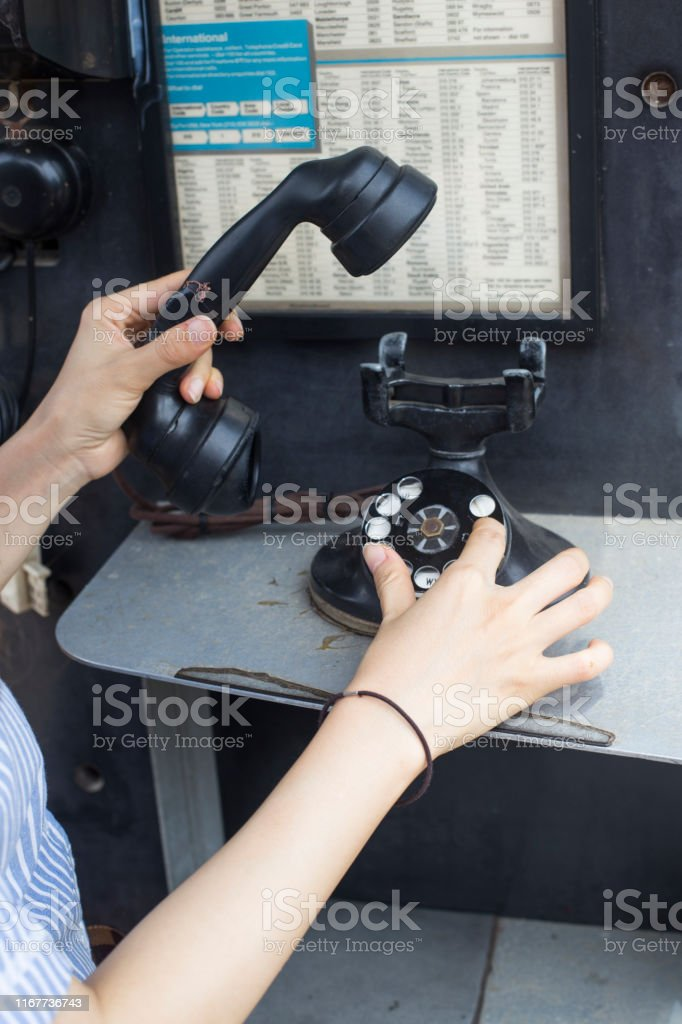Woman finger dialing a rotary dial telephone. woman hand hanging up...