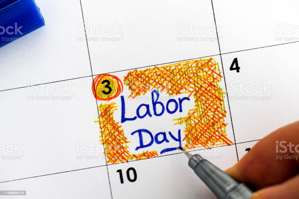 Woman Fingers With Blue Pen Writing Reminder Labor Day In Calendar