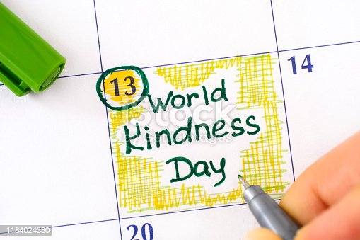 Woman fingers with green pen writing reminder World Kindness Day in calendar. November 13.