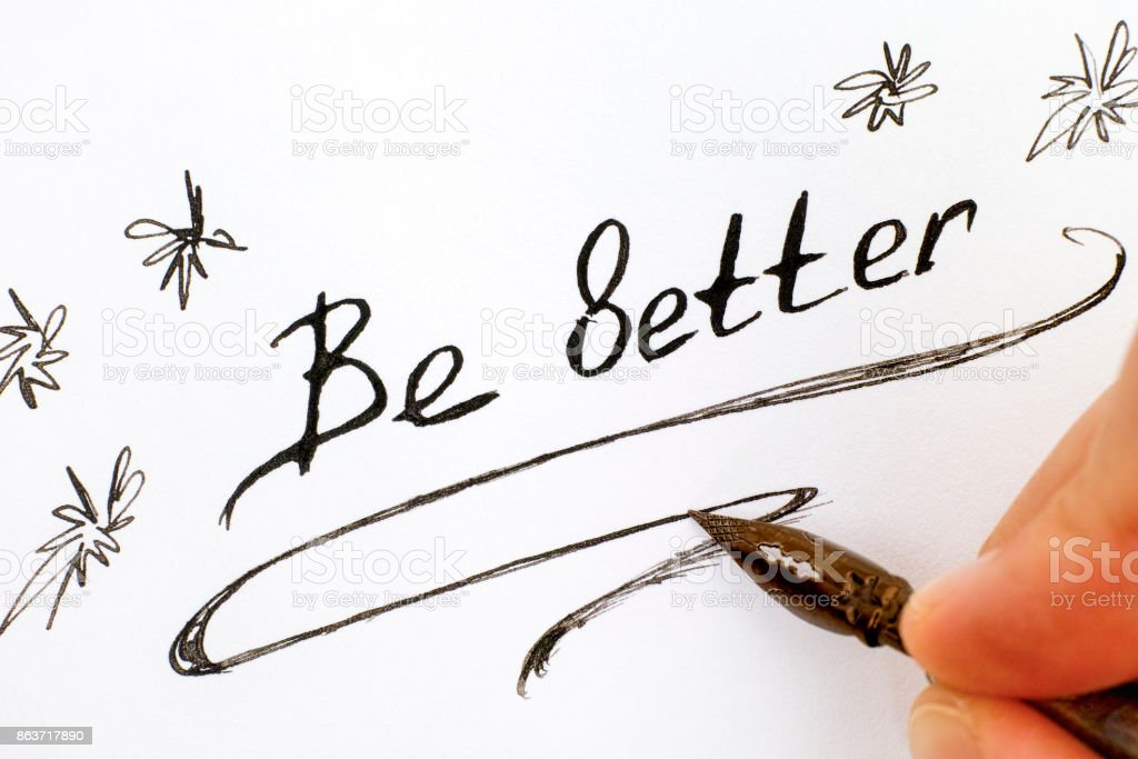 Woman fingers with pen writing phrase Be Better. stock photo