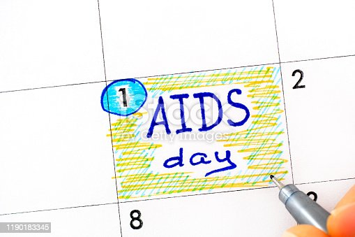 istock Woman fingers with pen writing reminder AIDS Day in calendar. December 01. 1190183345
