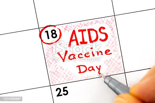 istock Woman fingers with pen writing reminder AIDS Vaccine Day in calendar. May 18. 1224355997