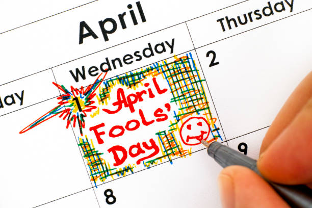 woman fingers with pen writing reminder april fools day in calendar. - april fools stock pictures, royalty-free photos & images