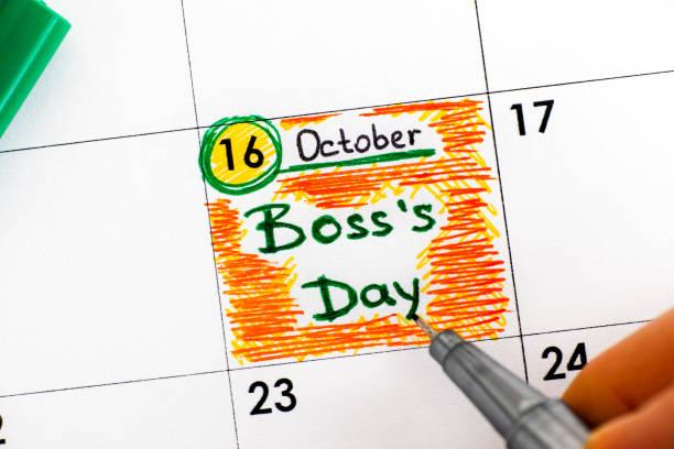 dedos de mujer con pluma escritura día de recordatorio jefe en el calendario. - boss's day fotografías e imágenes de stock