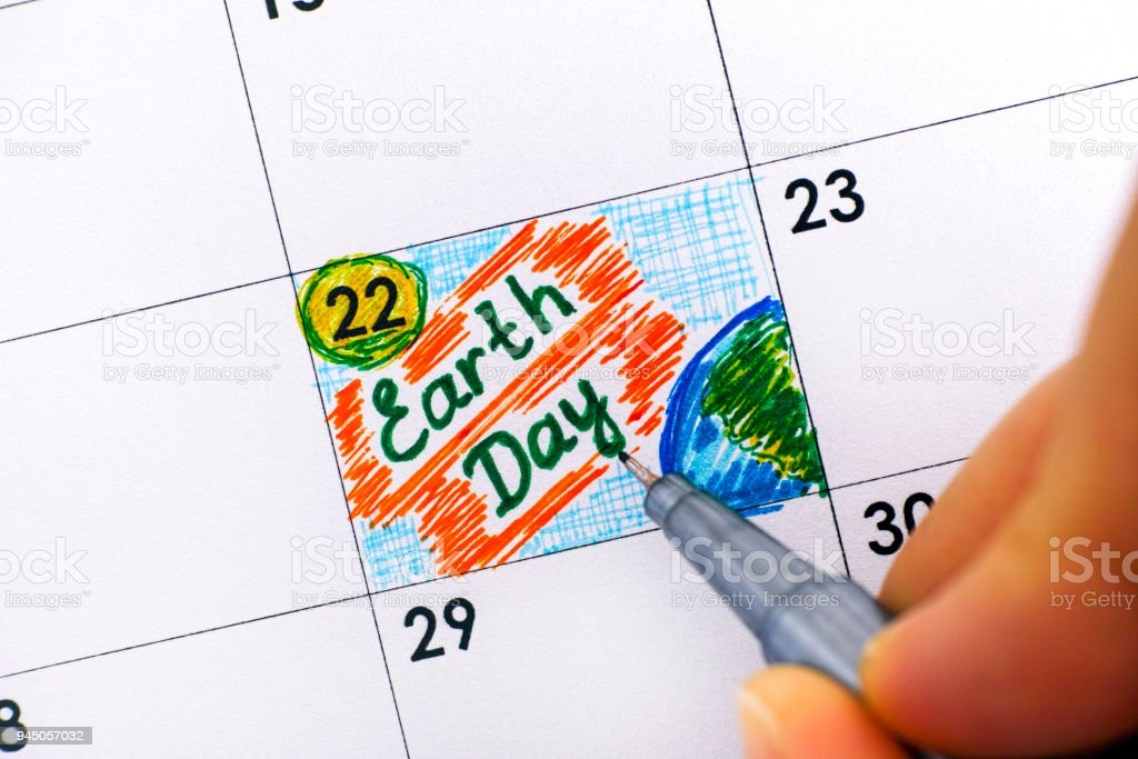 Woman fingers with pen writing reminder Earth Day in calendar. stock photo