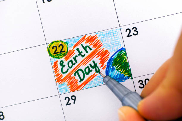 woman fingers with pen writing reminder earth day in calendar. - earth day stock pictures, royalty-free photos & images
