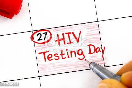 istock Woman fingers with pen writing reminder HIV Testing Day in calendar. June 27 1250283547