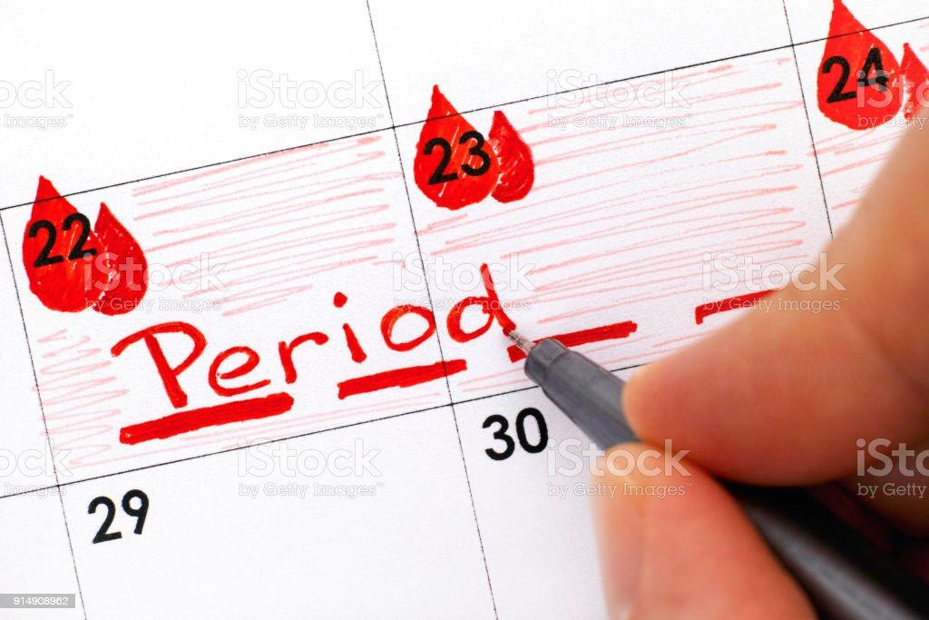 Dedos de mujer con pluma escritura recordatorio periodo calendario. - foto de stock