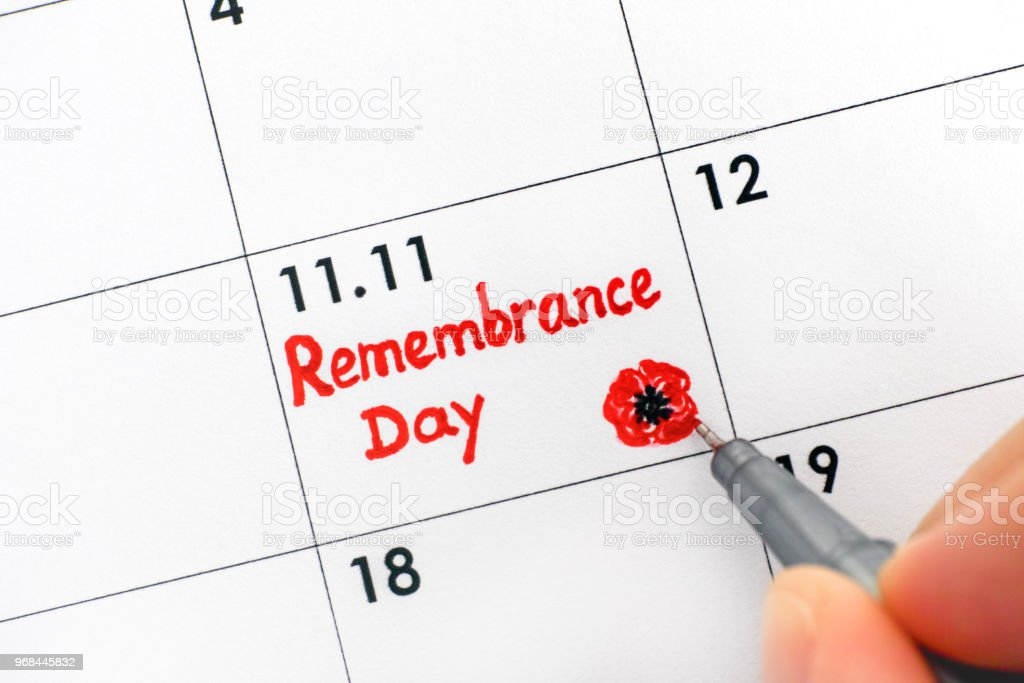 Woman fingers with pen writing reminder Remembrance Day in calendar. Close-up. stock photo