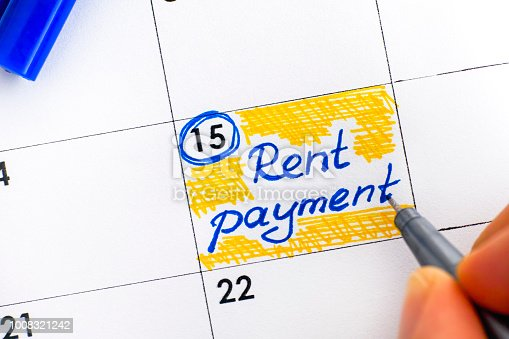 Woman fingers with pen writing reminder Rent Payment in calendar. Close-up.