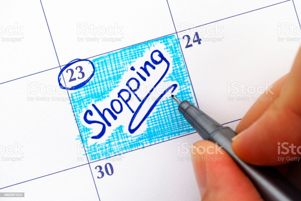 Woman fingers with pen writing reminder Shopping in calendar. royalty-free stock photo