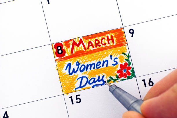 Woman fingers with pen writing reminder Women's day in calendar. stock photo
