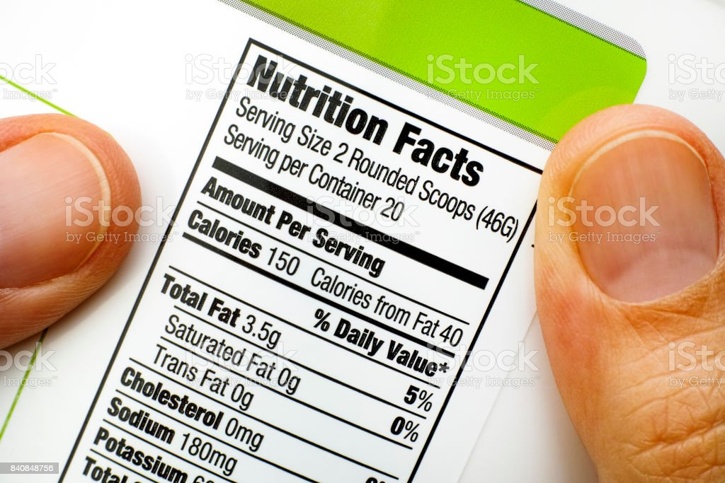 Woman fingers with protein jar. Reading nutrition facts stock photo
