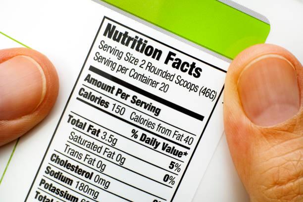 de vingers van de vrouw met eiwit pot. lezing voeding feiten - ingrediënt stockfoto's en -beelden
