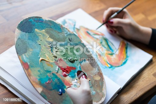 istock Woman finishing a painting 1091888262