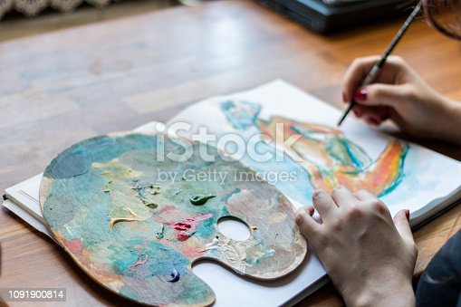937983086 istock photo Woman finishing a painting 1091900814