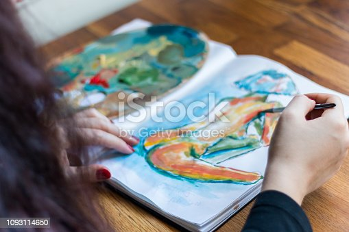 istock Woman finishing a painting 1093114650