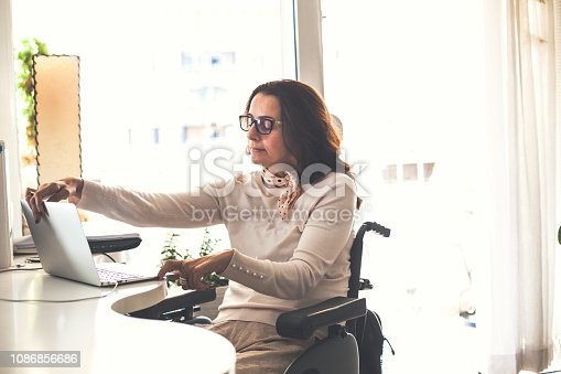 Woman with physical disability is closing her laptop at the end of working day.