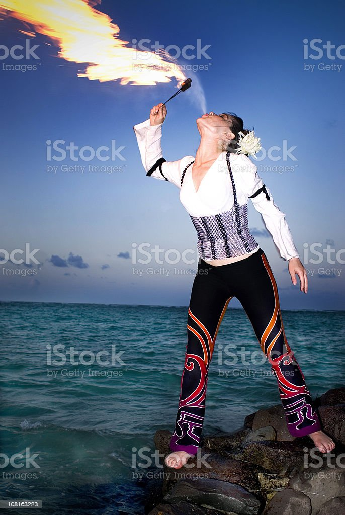 Woman Fire Breathing on Tropical Beach royalty-free stock photo