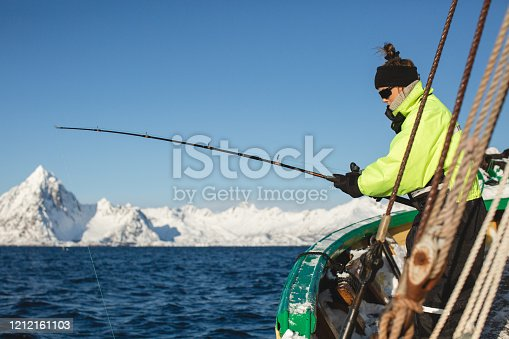 155674939 istock photo Woman fishing on boat in Lofoten, Norway. 1212161103