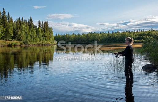 istock Woman fishing on the river in the summer evening 1175408985