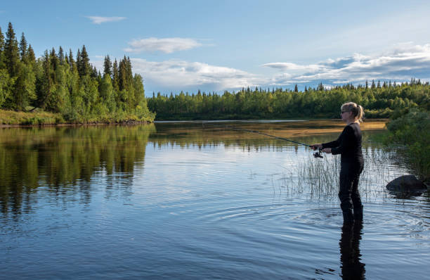 Woman fishing on the river in the summer evening stock photo