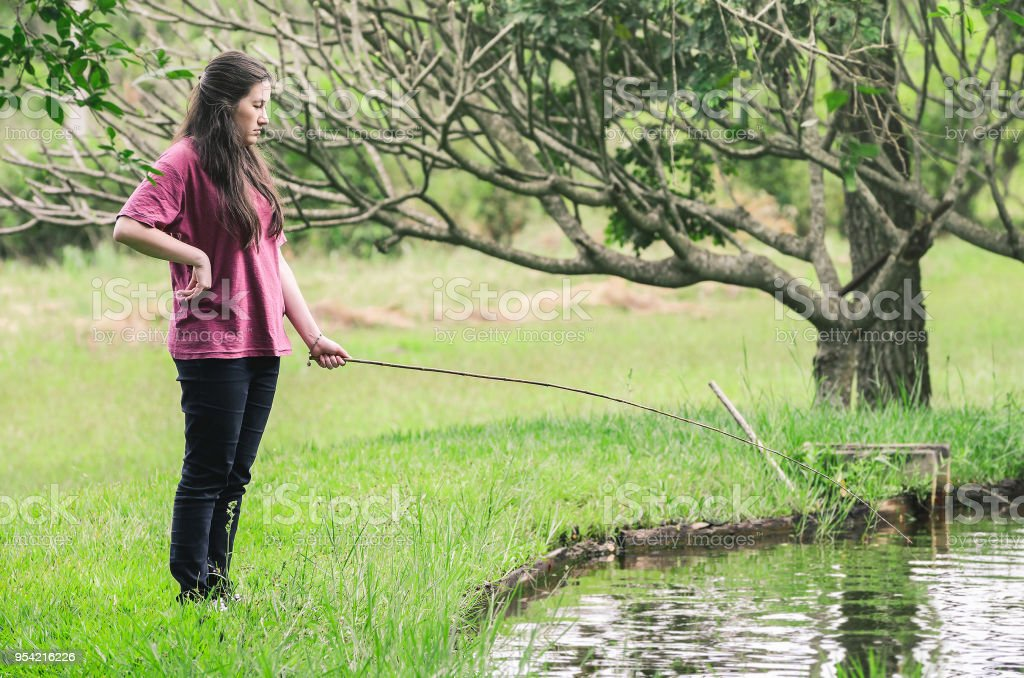 Woman fishing with anxiety expression, seriously, standing in front of the lake, holding a bamboo fishing rod waiting patiently to catch a fish. stock photo