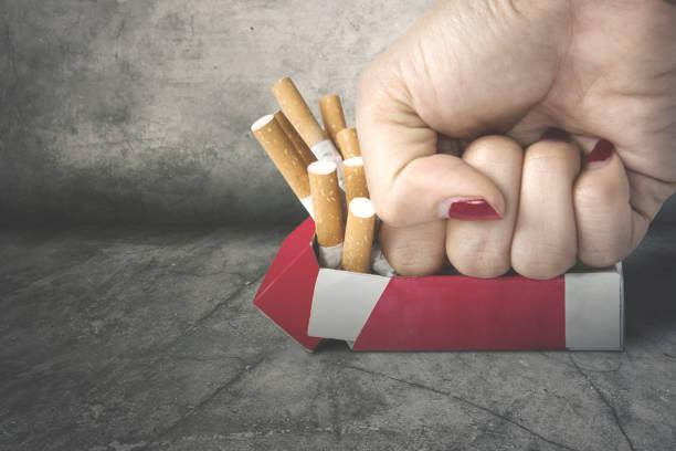 Woman fist crushing cigarettes stock photo