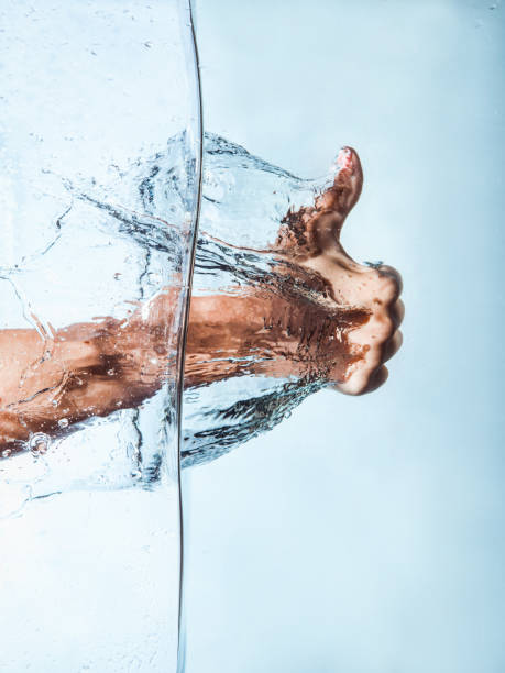 Woman Fist through the Blue Water and splashing drops Woman Fist through the Blue Water and splashing drops,Like hand sign sopaatervinning stock pictures, royalty-free photos & images