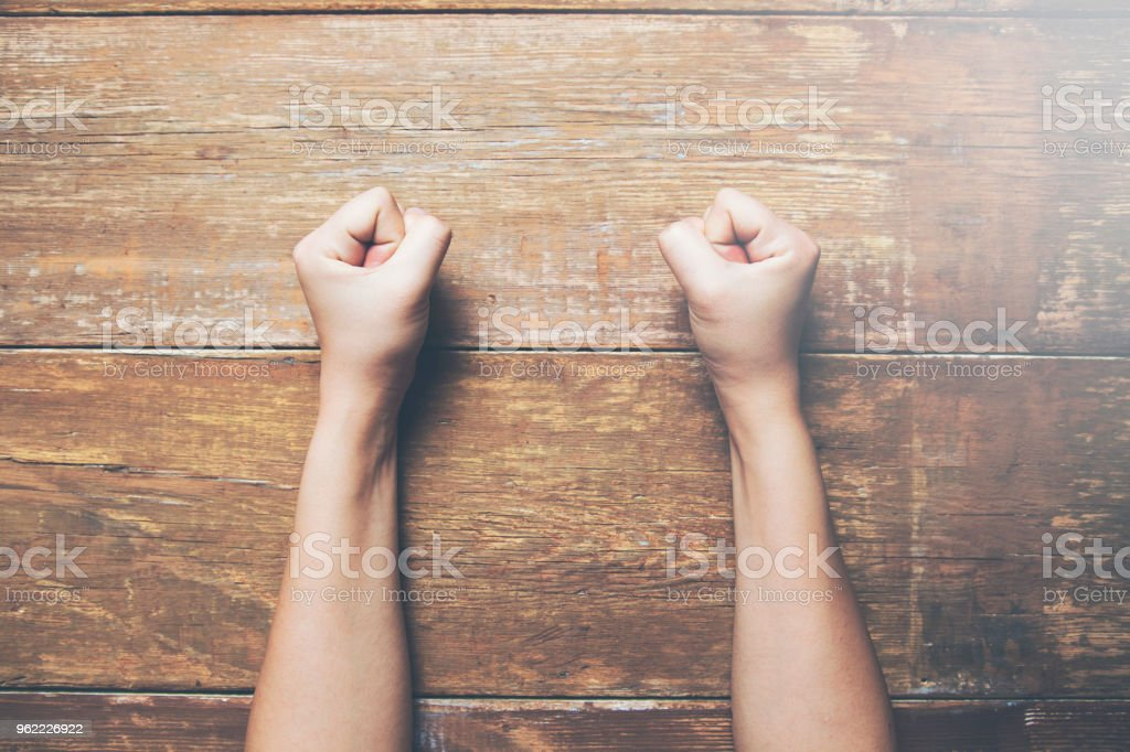 woman fists clenched on a wooden table in anger
