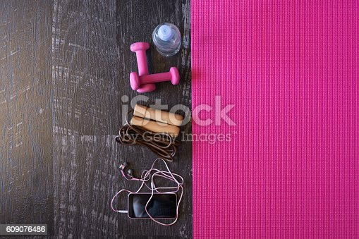 istock Woman fitness equipment and pink yoga mat on wooden background 609076486