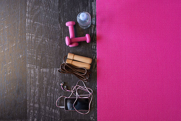 woman fitness equipment and pink yoga mat on wooden background - rosa training stock-fotos und bilder