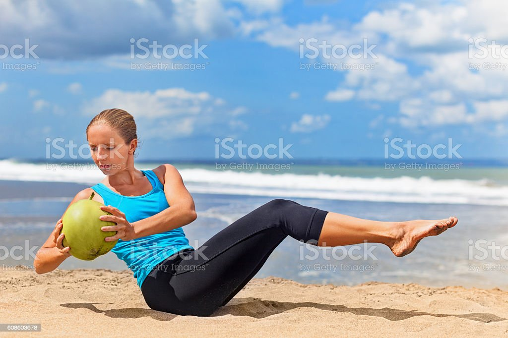 Woman fitness exercise with green coconuts on ocean beach stock photo
