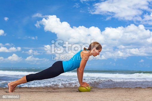 istock Woman fitness exercise with raw coconut on ocean beach 607885552